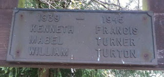 Bronze plaque with raised lettering set on wooden beam.