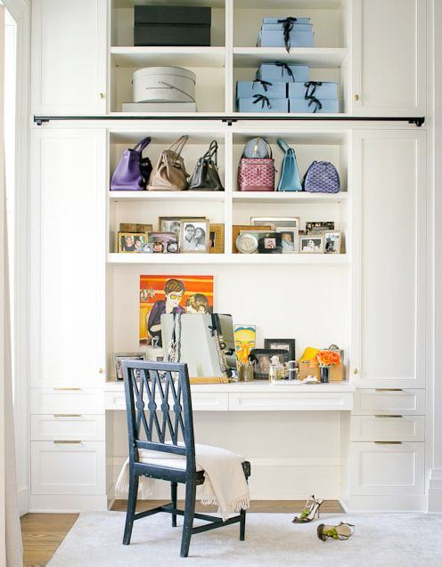 white built in desk/vanity in a walk in closet with a blue wooden chair. The shelves above the desk hold pictures, handbags and decorative boxes