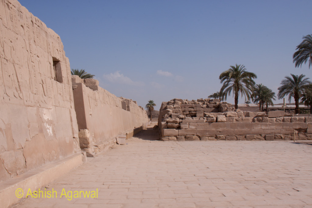 An isolated section of the Karnak temple in Luxor, along with some palm trees