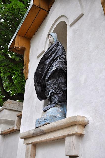 """Kapliczka Matki Boskiej w murze parkowym, prace konserwacyjne - niecodzienna """"sukienka"""" MB. Foto. 2013 r. KW."""