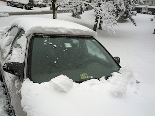 Car is still mostly snow-covered, but the sheet has been removed and the windshield is completely clear.