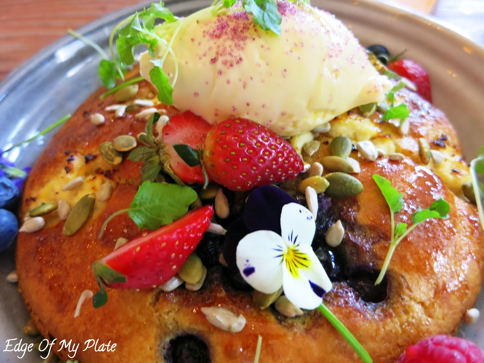 Blueberry and ricotta hotcake with berries, organic maple, seeds and double cream