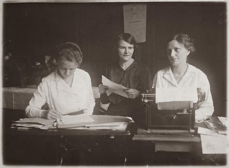 Drei Damen im Büro mit Schreibmaschine, Wandkalender und Papierstapel
