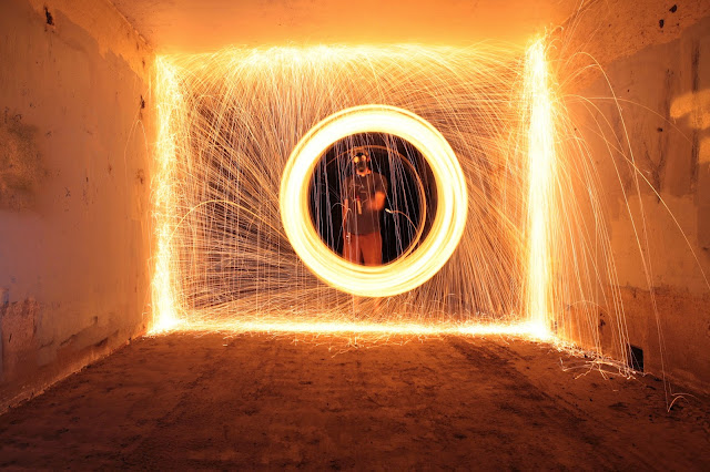 A long exposure photograph of burning steel wool in a tunnel.