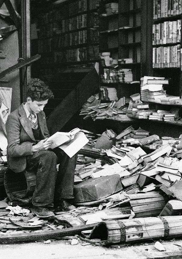 boy reading books after the bombing of London in WW2