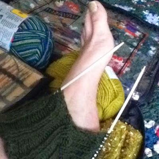 Foot sticking out through the heel opening of forest-green socks in progress