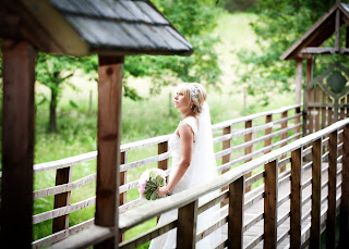 Bride poses on a bridge wearing a lace bridal gown and veil with hair band accessory