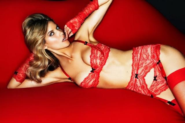 femme blonde allongée sur canapé rouge en lingerie Myla en dentelel rouge sexy et petits noeuds noir. Elle porte des gants et mitaines en dentelle rouge vanessa lekpa