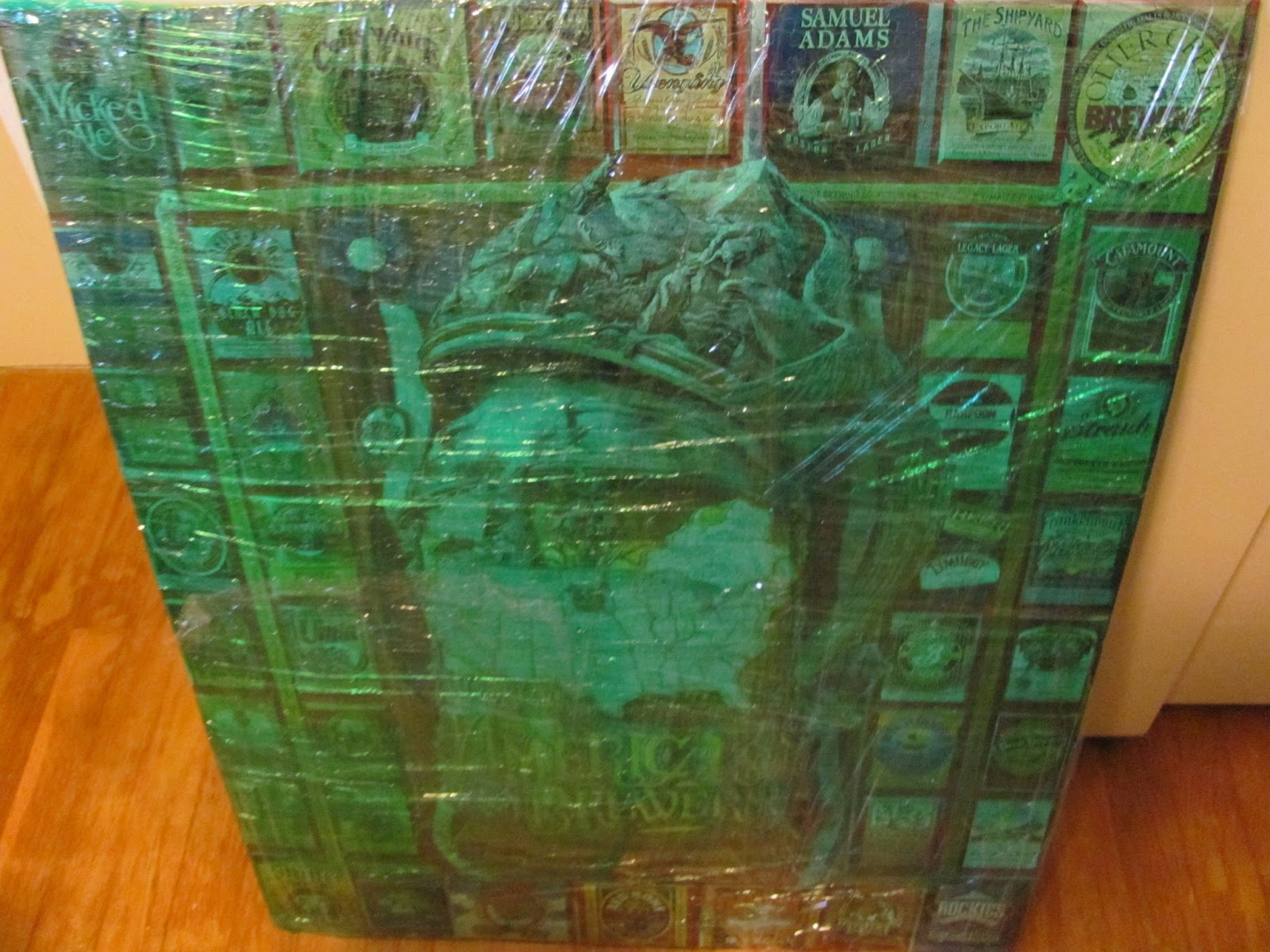 Large beer logo puzzle framed and wrapped in green plastic