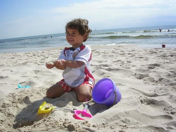 barn på sandstrand med sand i händerna. foto: Reb Dutius
