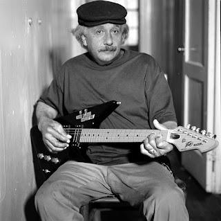 Einstein sentado em uma cadeira tocando guitarra.