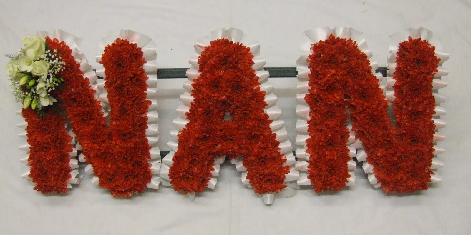 Rjs florist name tributes moni with foliage edging and lemon spray izmirmasajfo