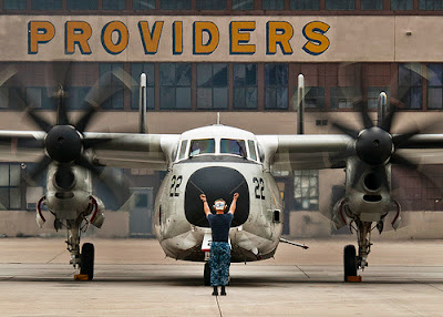 A Sailor directs a C-2A Greyhound.  Coronado, Calif. Photo by The U.S.Navy