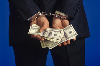 Picture of the back of a handcuffed man in business suite holding money.