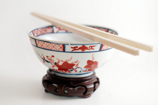 A china bowl with chopsticks resting on top