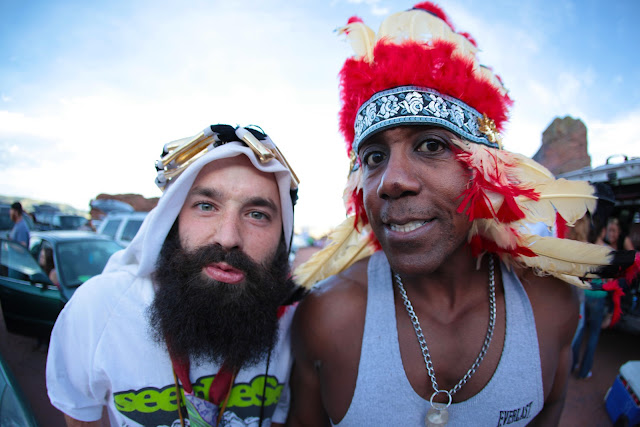 A guy wearing a Native American headdress and a guy wearing a Saudi headdress.
