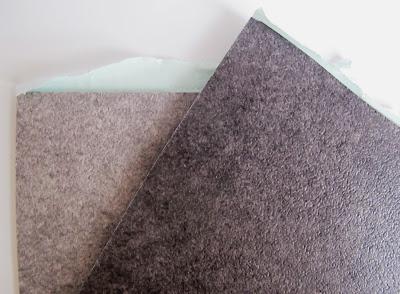 Two grey self-adhesive vinyl tile samples.