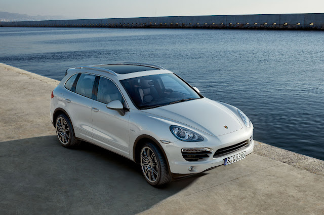 Front 3/4 view from above of white 2011 Porsche Cayenne Hybrid parked next to water
