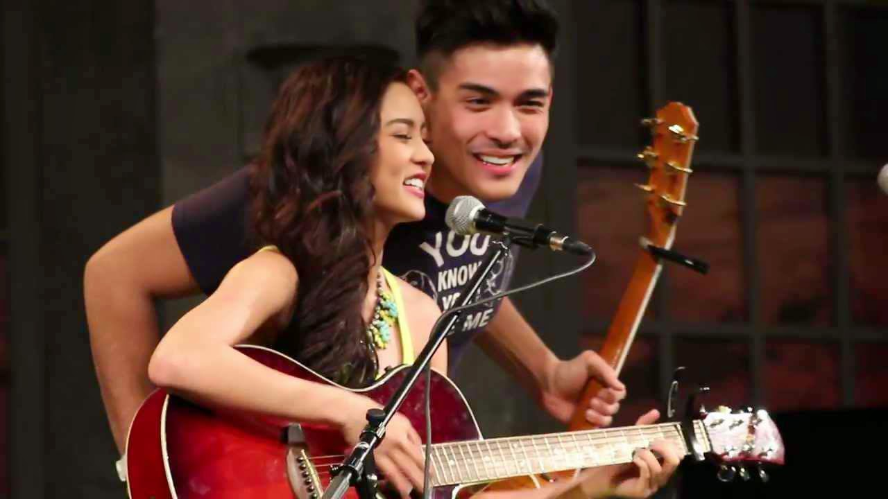 Kim and Xian playing guitar while singing