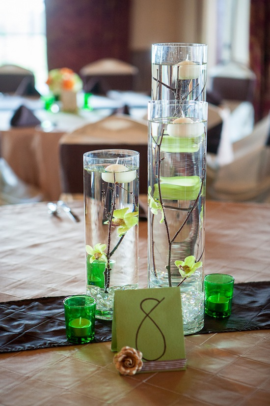 glass centeriece with floating candles and green votives plus the table number
