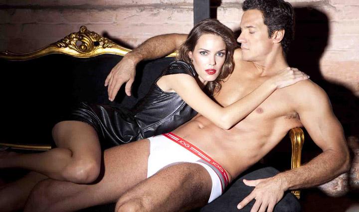 O ator posou ao lado de uma modelo, deitado em um sofá
