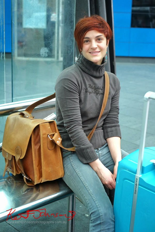 An Italian traveller at Central Bus Interchange, leather satchel and blue Samsonite case, short red hair, jeans and polo neck jumper.