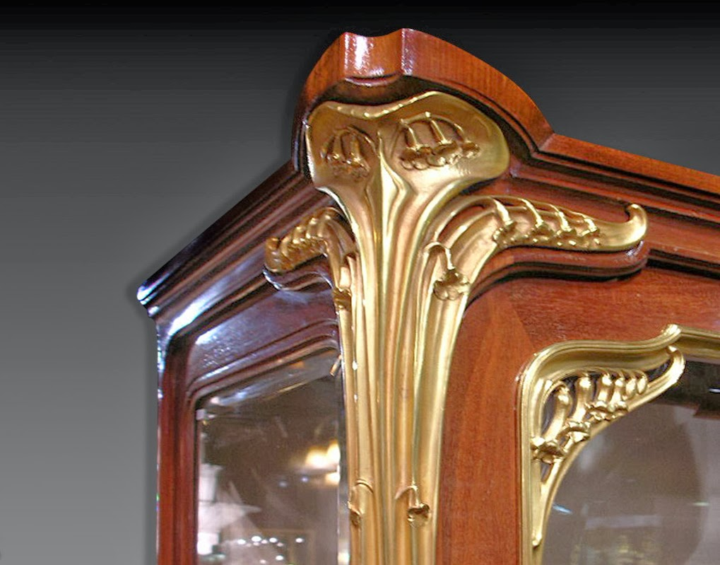 Mahogany display cabinet strictly shaped with the fine, bronze decoration. Framed design is softened by the presence of glowing stylised flowers rolling over the corners, the sides and footboards