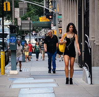 Woman in the city walking along with other pedestrians.