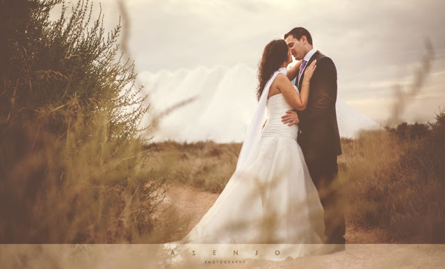 novios besandose junto montañas de sal