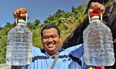 For consumption: Nor Suhaimi showing two large plastic bottles filled with the mineral water.