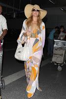 Paris Hilton wearing a 70s dress and a hat