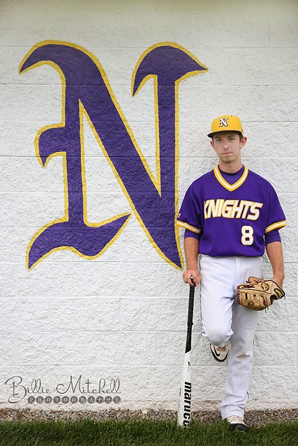 baseball player leaning on dugout wall wearing purple jersey and holding bat and glove