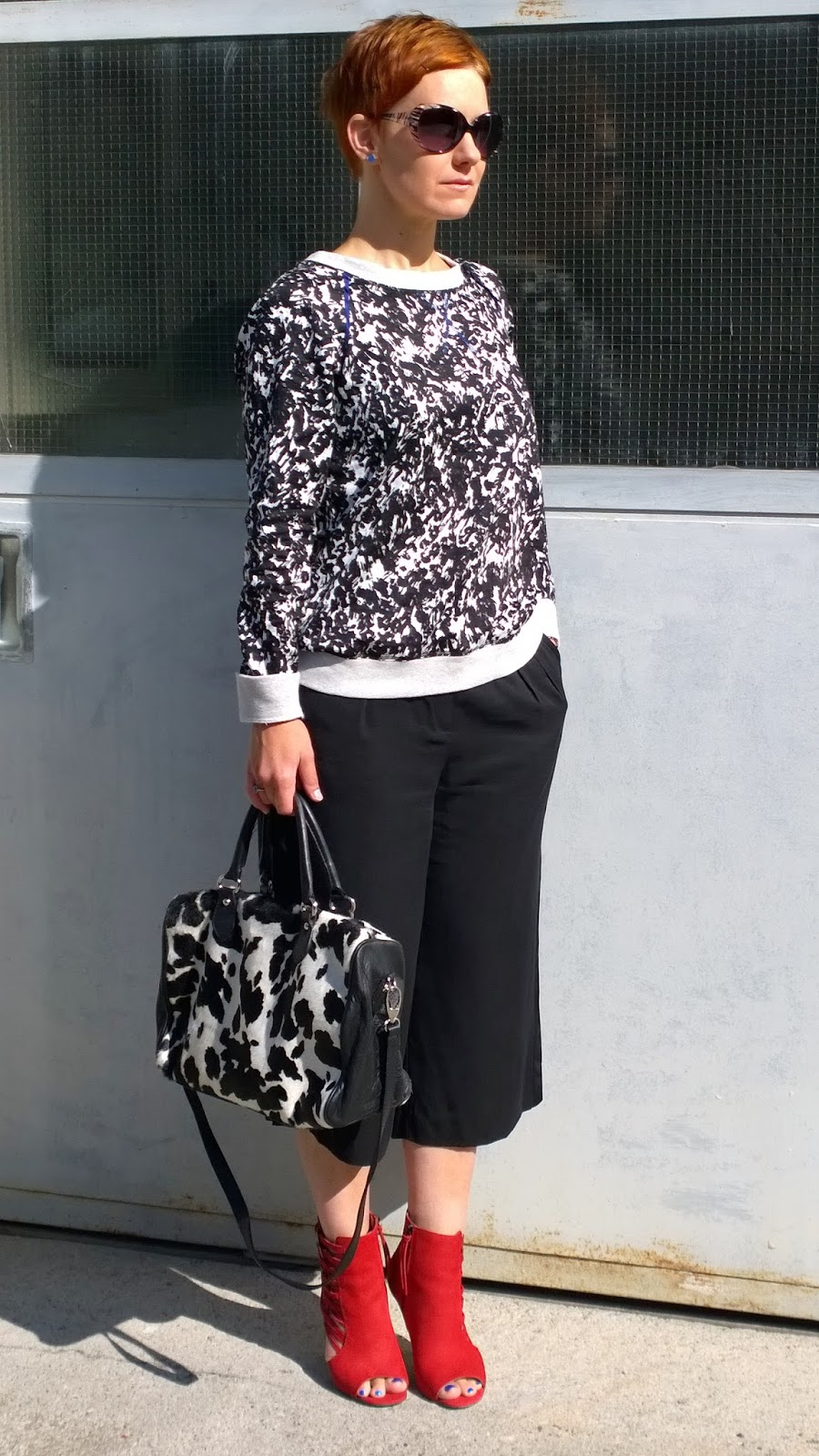 cow print bag, black and white splash pattern sweater, zebra sunglasses, red open toe booties, culottes