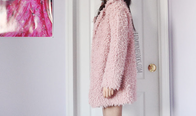 A pastel-hued spring outfit, featuring SheIn's dusty pink faux fur longline coat, white crochet mock neck lace floral romper, and white Jeffrey Campbell Lita Spike dupe platform booties.