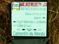 Suport de fusta amb la placa identificativa del GR 97 i del PR C-142 davant el Cementiri de Marata