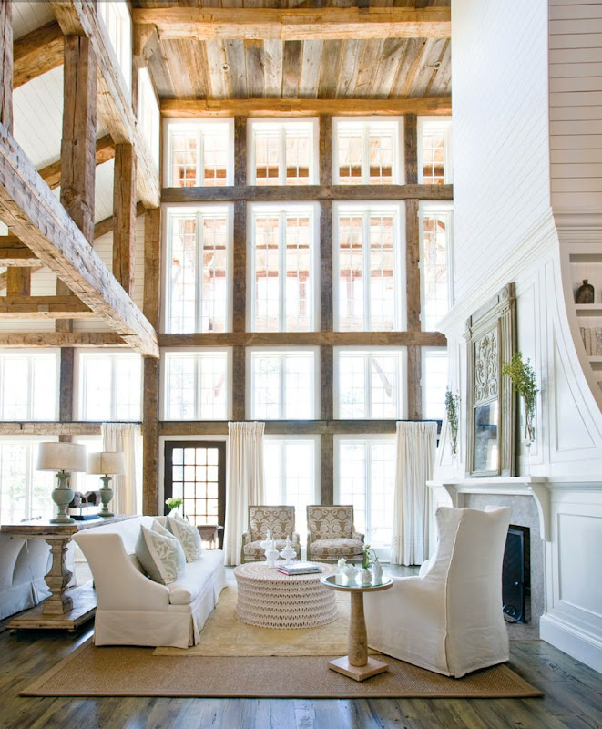 Living room with reclaimed wood beams, a super tall white wood paneled and plank covered fireplace, 2.5 story windows, a wood floor with a sea grass rug, a white sofa with matching armchair, and a round ottoman