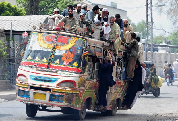 Superlotação de ônibus no Paquistão, mais de 15 pessoas são transportadas sobre o teto do veículo