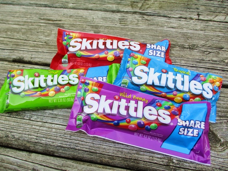 Pile of Original Skittles, Sour Skittles, Tropical Skittles, and Wild Berry Skittles.