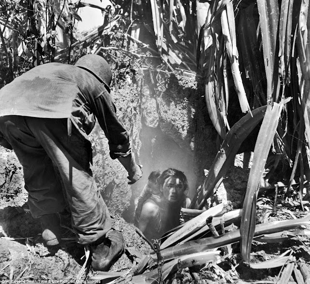 A US soldier offers his hand to a woman leaving a cave where she had hidden with her child during the battle between Japanese and American forces. Saipan, 1944