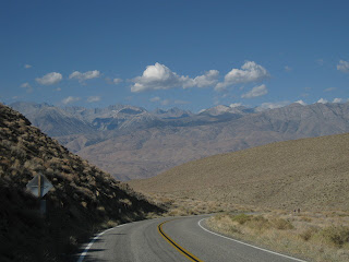 Two cyclists climbing through the desert landscape along California State Route 168 near Big Pine, California