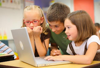 children gathered around a computer in class
