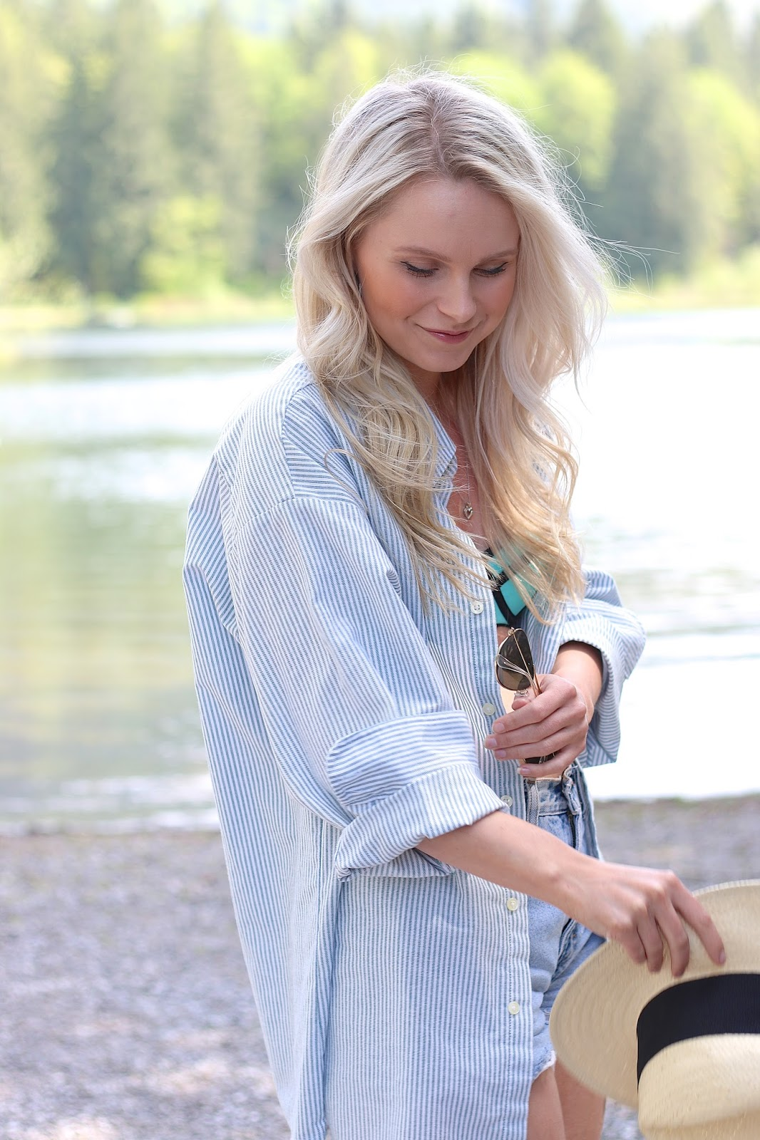 a blonde girl stand next to a beautiful lake in vintage levis shorts