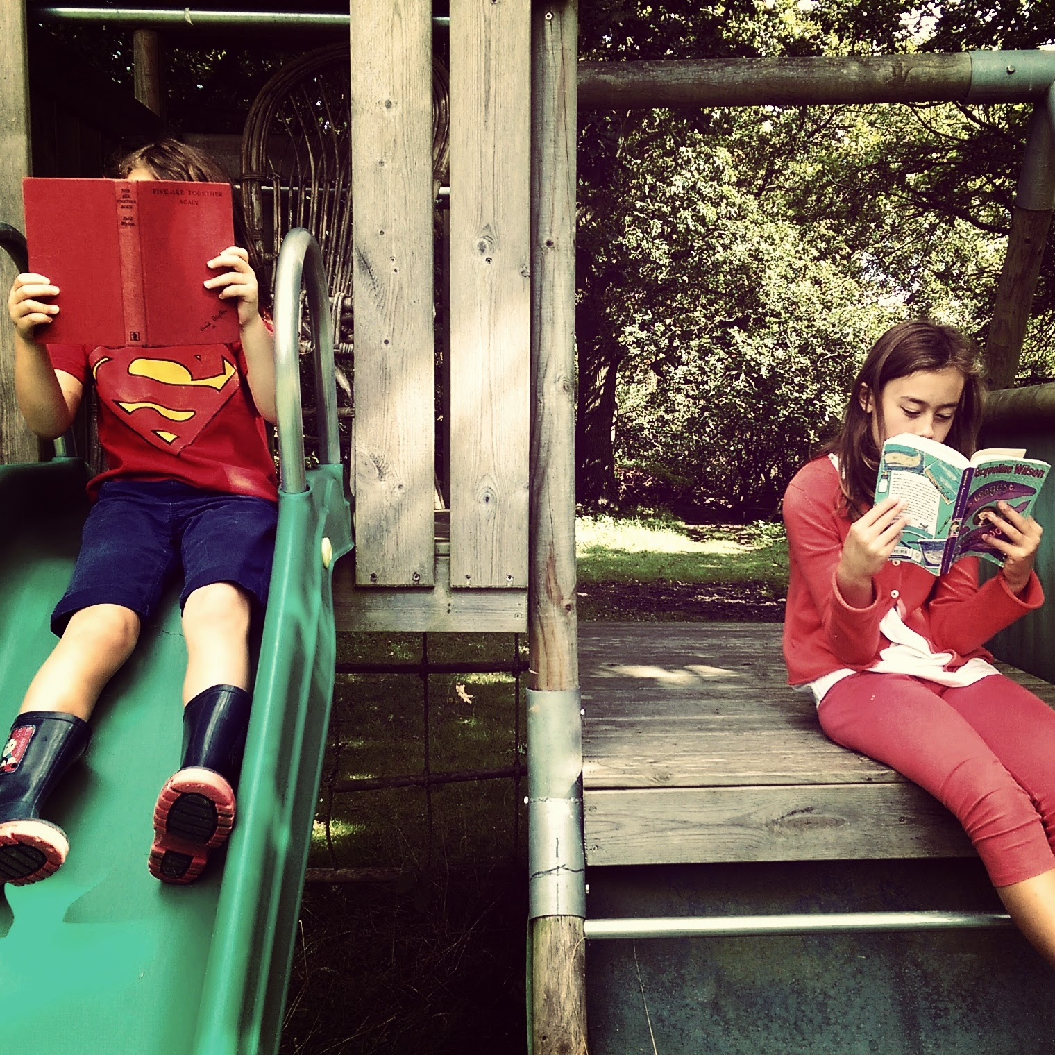 Two girls reading books on play equipment
