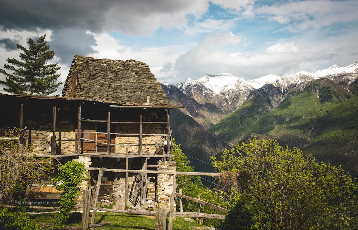 Steinhaus vor schneebedeckten Bergen