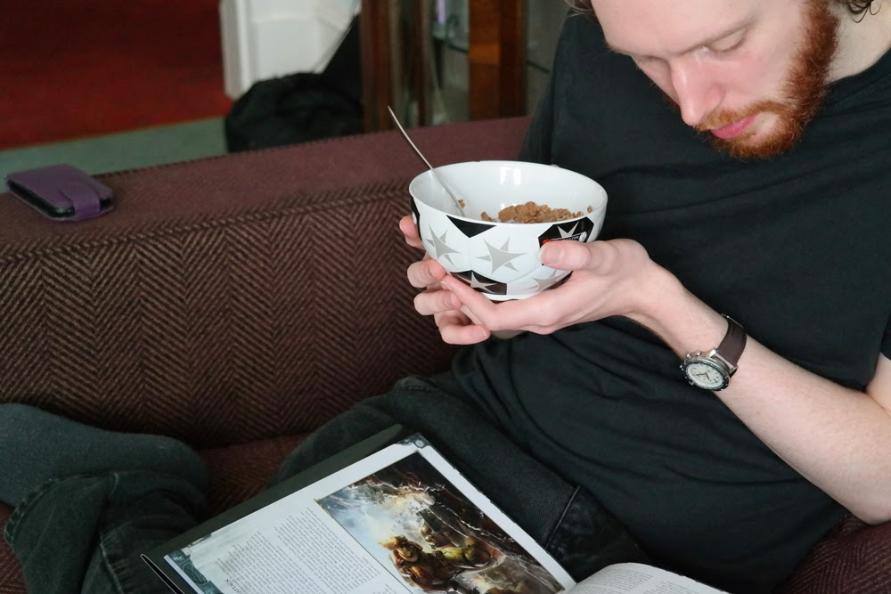 Steve cradling cereal bowl and reading book