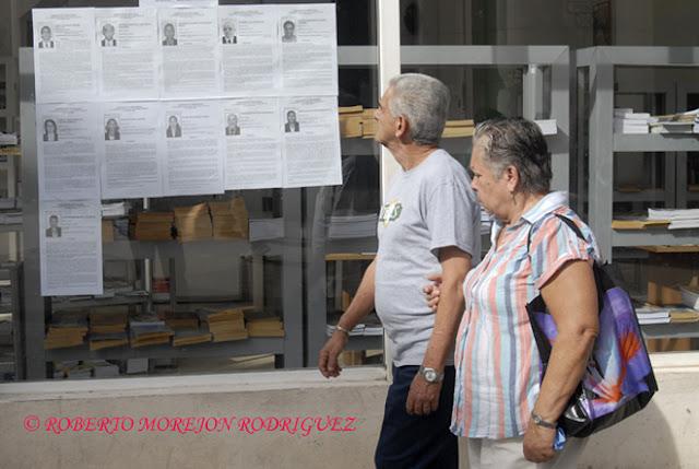 Dos personas observan las fotos y biografías de los candidatos al Parlamento Cubano expuestas en la calle Obispo, en La Habana, Cuba.