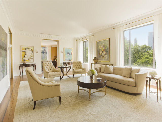Living room in an upper east side apartment with wood floors with a cream area rug, sofa and arm chairs with dark wood accents and matching dark wood side tables