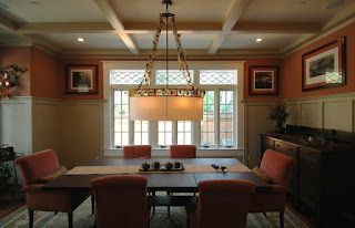Classic Details in the Dining Room with Red Upholstered Dining Chairs and Wooden Table under Wide Pendant Light