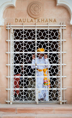 A man peers our from behind an elaborately made white iron door in the Mehrangarh Fort, Rajasthan, India