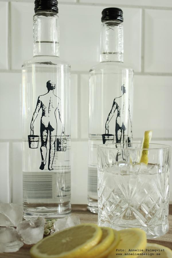 glasflaska med mineralvatten, prisbelönt vatten från danska källan krusmölle, glasflaskor, webbutik, webbutiker, webshop, vatten, flaska, flaskor, flaska med en man på, citron, citroner, på bordet,